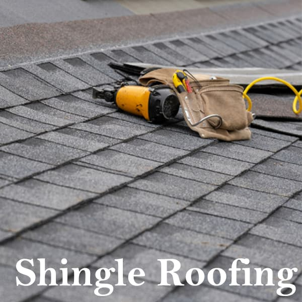 tools for shingle roofing sitting on a roof